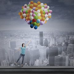 Asian woman flying with balloons