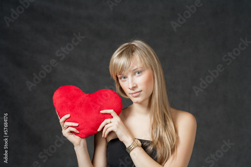 American Blond haired Woman with a Heart-Shaped Cushion on dark