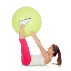 Attractive woman doing pilates with a big green ball