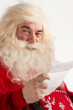 Portrait of happy Santa Claus holding Christmas letter and looki