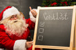 Santa Claus sitting near chalkboard