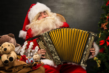 Santa Claus sitting in armchair near Christmas Tree at home and