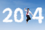 Happy businessman jumps with clouds of 2014