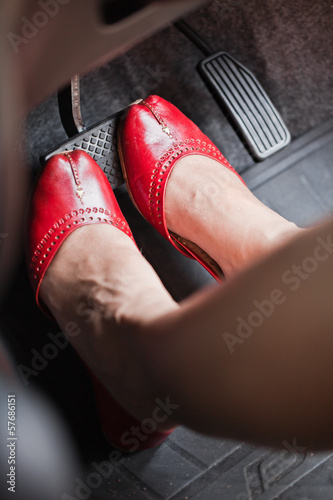A woman's foot depressing the brake pedal of a car
