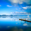 Wooden pier or jetty and blue lake sunset. Versilia, Italy