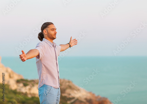 man stands on a cliff near the sea at sunset