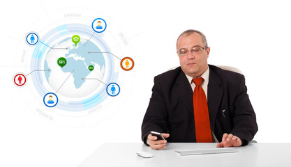 businessman sitting at desk and holding a mobilephone with globe