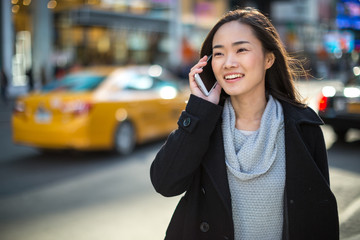 Asian woman in New York City talking on cellphone