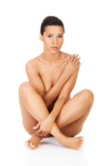 Beautiful and naked women sitting and covering her nudity by her