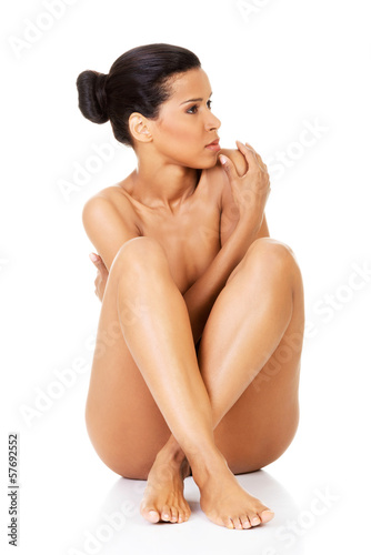 Beautiful woman sitting naked and covering her body with her arm