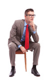 seated young business man looks away pensively
