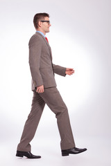 side of young business man walking straight forward