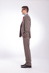 side of young business man with hands in pockets