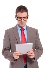 young business man holds tablet and looks at it