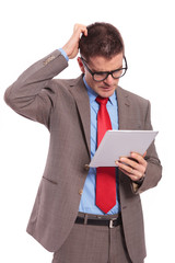 young business man holds tablet and scratches head