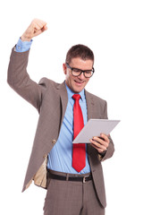 young business man holds tablet and cheering