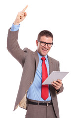 young business man holds tablet and cheers with finger up