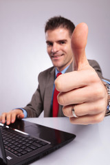 young business man at laptop shows thumb up