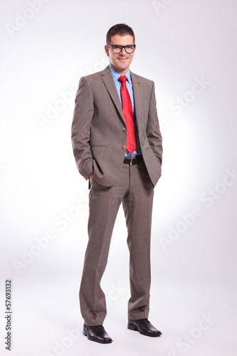 young business man smiles with both hands in pockets
