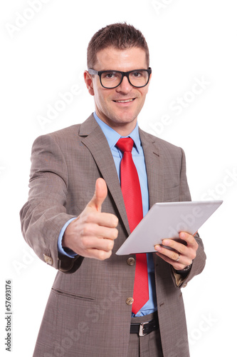 young business man holds tablet and shows thumb up
