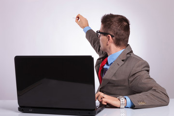 young business man writes on the back while at laptop