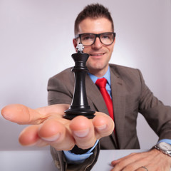 young business man holds a black chess king in hand