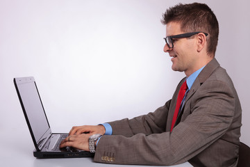 side of young business man working on laptop