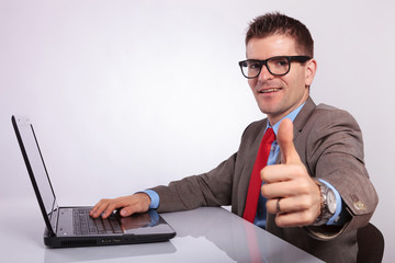 side of young business man at laptop, showing thumb up