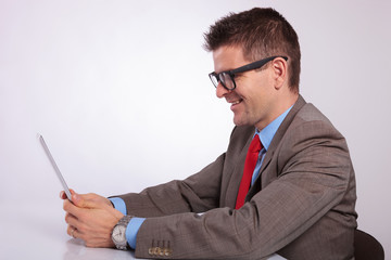 side of young business man smiling at his tablet