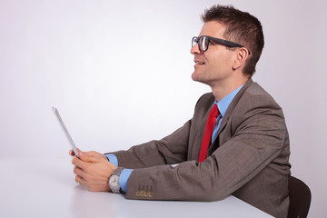 side of young business man with tablet, looking up