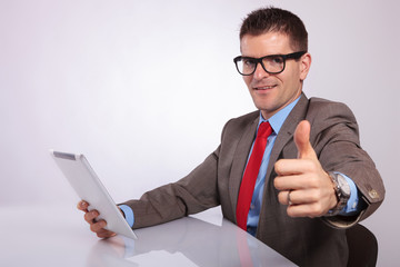 side of young business man with tablet, showing thumb up