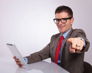 side of young business man with tablet, pointing at you