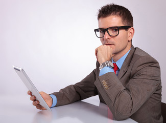 side of pensive young business man with tablet looking at you