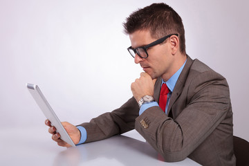 side of young business man looking pensively at his tablet