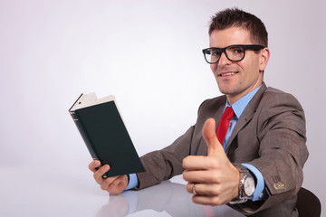 side of young business man with book showing thumb up