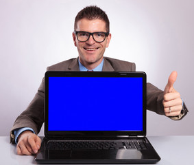 young business man presents his laptop with thumb up