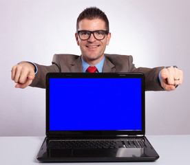 young business man presents laptop and points with both hands at
