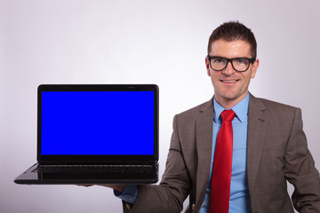 young business man presents laptop while smiling