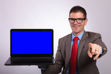 young business man presents a laptop and points at you