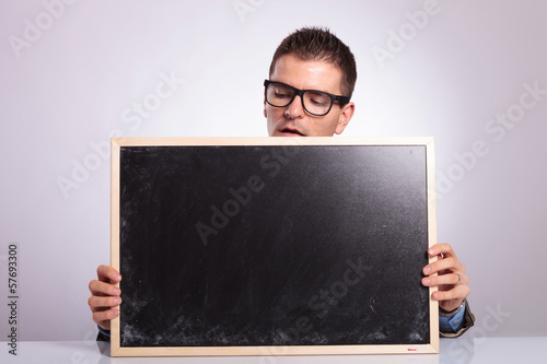 young business man holds a blank blackboard