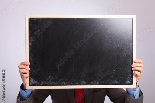 young business man holds blackboard in front of his face