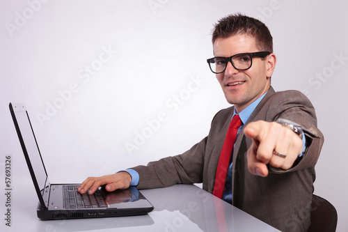 side of young business man at laptop, pointing at you