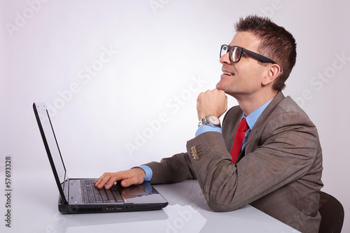 side of young business man with laptop, looking up with hand on