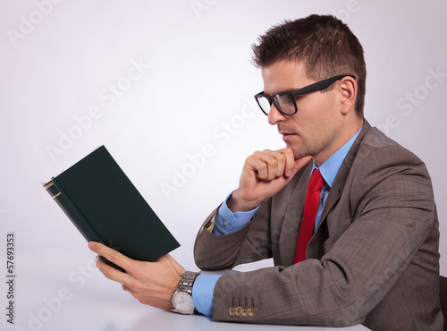 side of young business man reading a book pensively