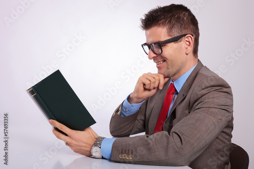 side of young business man reading a book with hand on chin