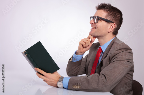 side of young business man daydreaming with book in hand