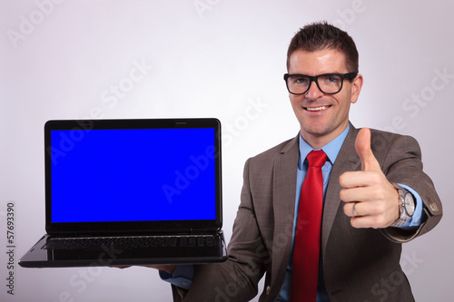 young business man presents laptop with thumb up