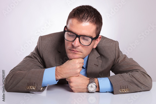 young business man sleeps on his fists at office