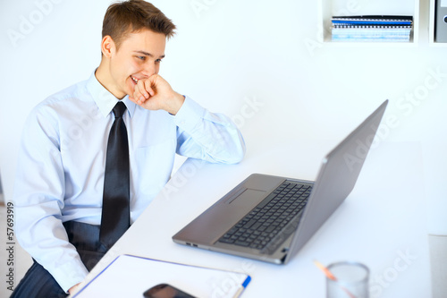 Young laughing businessman looking at the laptop screen