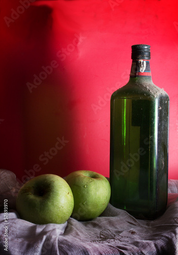 Antique wine or whiskey bottle with apples